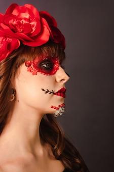 Макро портрет молодой девушки с макияжем dia de los muertos с серым фоном.