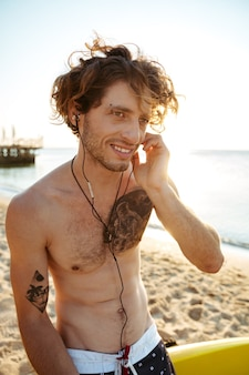 해변에서 서핑 보드에 앉아있는 동안 이어폰으로 젊은 잘 생긴 곱슬 서퍼 듣는 음악의 초상화를 닫습니다