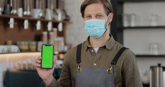 バーのカウンターの前に立って、カフェで右手に持っているカメラにスマートフォンの緑色の画面を表示しているフェイスマスクの若い男のバリスタの肖像画を閉じます。