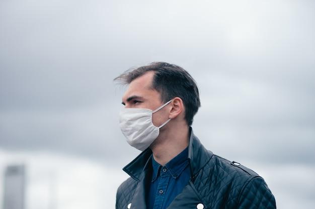 Закройте вверх. портрет молодого человека в защитной маске. концепция охраны здоровья