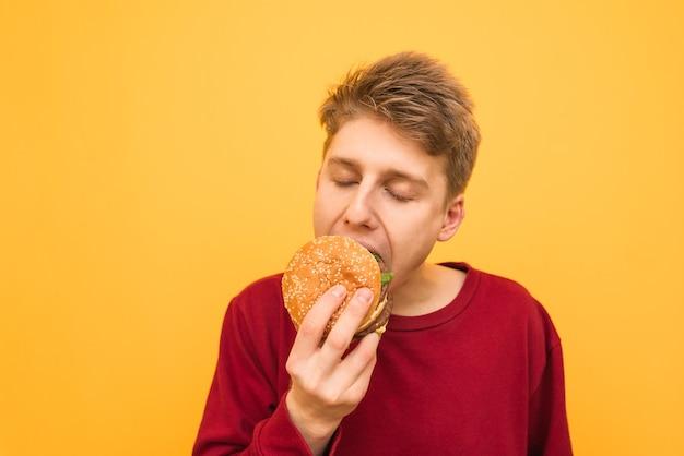 カジュアルな服装の若い男のクローズアップの肖像画はハンバーガーをかむ