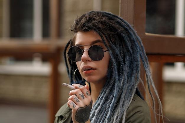 도시를 걷고 있는 카메라를 즐겁게 바라보며 향취를 가진 젊고 예쁜 웃는 여성의 초상화를 닫습니다. 소녀는 담배를 피우다