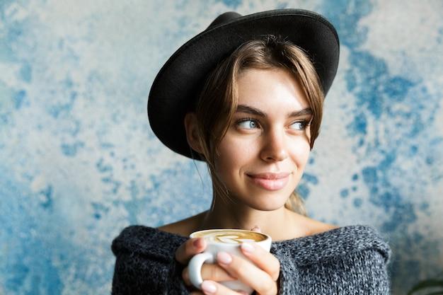 파란색 벽에 스웨터와 모자를 입은 젊은 여자의 초상화를 닫고, 멀리보고, 뜨거운 커피 한잔 들고