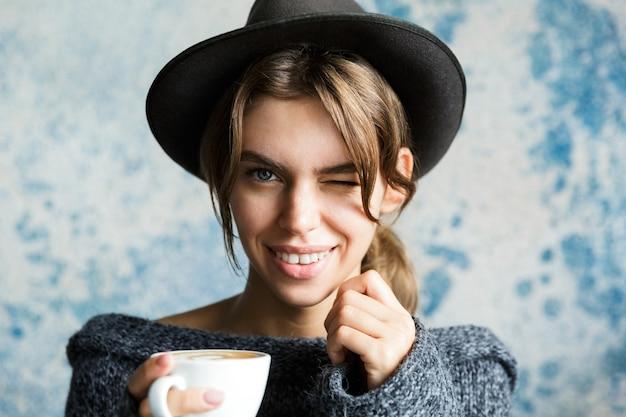 파란색 벽에 스웨터와 모자를 입은 젊은 여자의 초상화를 닫고, 뜨거운 커피 한잔 들고 윙크