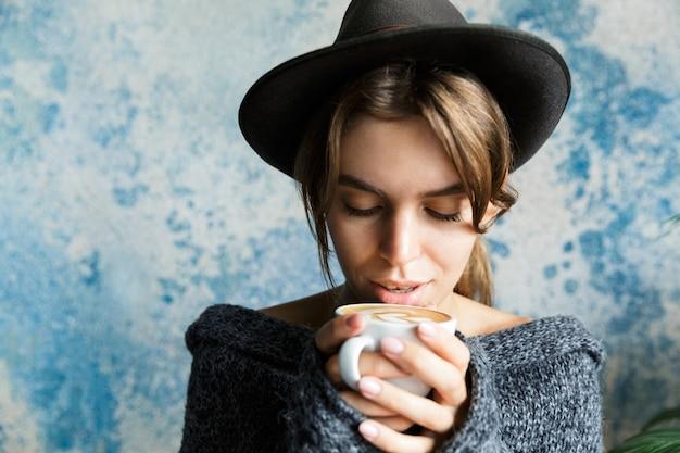 뜨거운 커피 한잔 들고 파란색 벽에 스웨터와 모자를 입은 젊은 여자의 초상화를 닫습니다