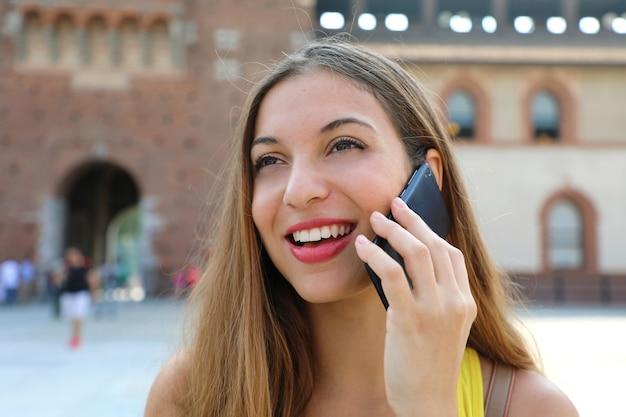 Крупным планом портрет молодой женщины разговаривает по телефону в милане в италии