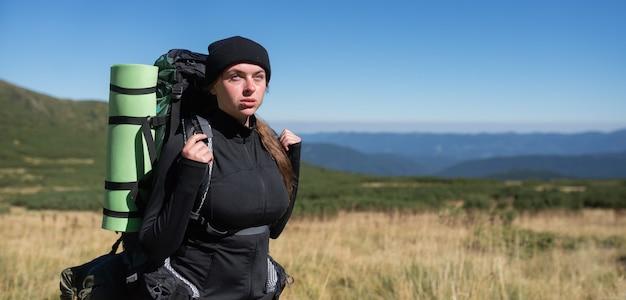 Крупным планом портрет молодой женщины турист с большим рюкзаком.