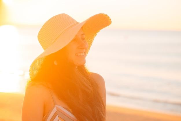 日光の下で帽子をかぶっている若い女性の肖像画を閉じます。