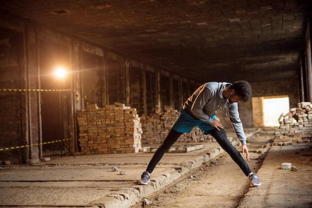 Закройте вверх по портрету активного афро-американского молодого привлекательного атлетического человека делая полную ногу протягивая разминку внутри покинутого места.