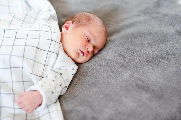 Портрет крупным планом очаровательного мальчика, спящего в постели, концепции 1-летнего ребенка.