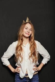 Крупным планом портрет очаровательны девушки с золотой короной, держа хана
