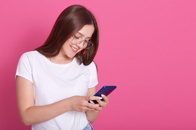 Закройте вверх по портрету сообщения прелестной женщины печатая к ее друзьям или husbaund. молодая женщина держит мобильный телефон