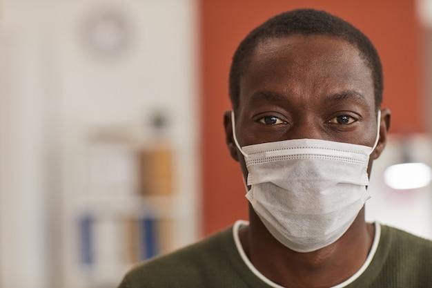 マスクを着用し、オフィスでの作業中にカメラを見ている大人のアフリカ系アメリカ人男性の肖像画をクローズアップ、コピースペース