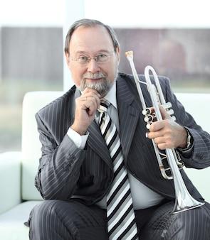 Закройте вверх. портрет взрослого музыканта мужского пола с трубой.