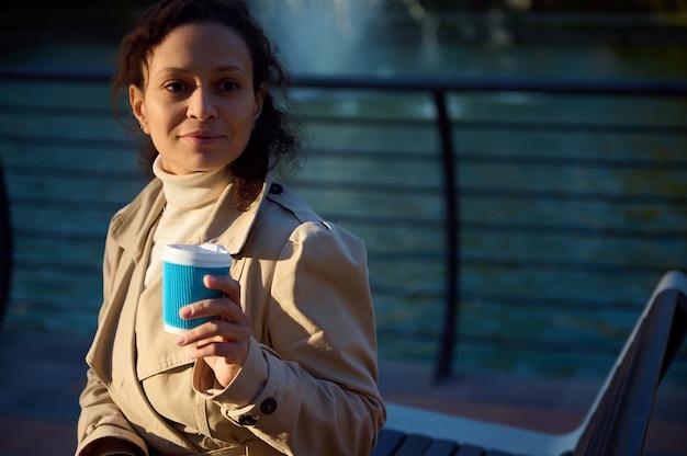 베이지색 트렌치 코트를 입은 아프리카계 미국인 고요한 예쁜 여성의 클로즈업 초상화는 테이크아웃 재활용 종이컵과 뜨거운 음료를 들고 호수 배경에서 쉬고 있습니다. 가을 배경