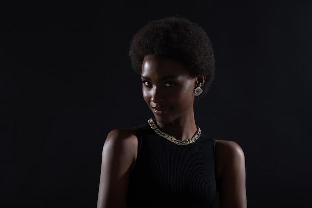Крупным планом портрет афро-американской женщины с афро-прической на черном студийном фоне