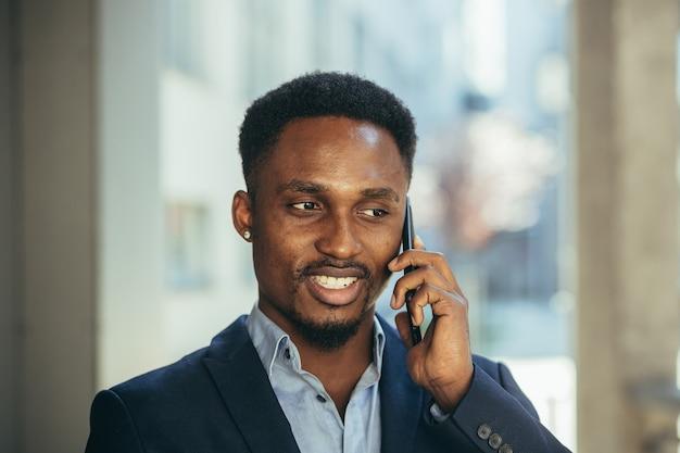 電話で話し、ビジネススーツの成功から笑顔のアフリカのビジネスマンの肖像画をクローズアップ