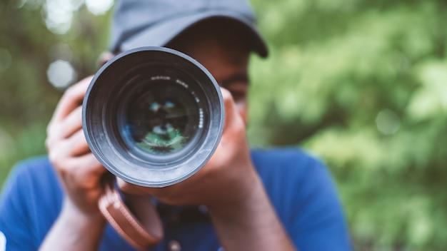 Крупным планом портрет африканского фотографа фотографировать с цифровой камерой. 16: 9 стиль