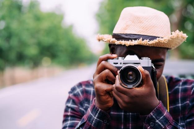 アフリカの旅行者とデジタルカメラで写真を撮る写真家の肖像画を間近します。