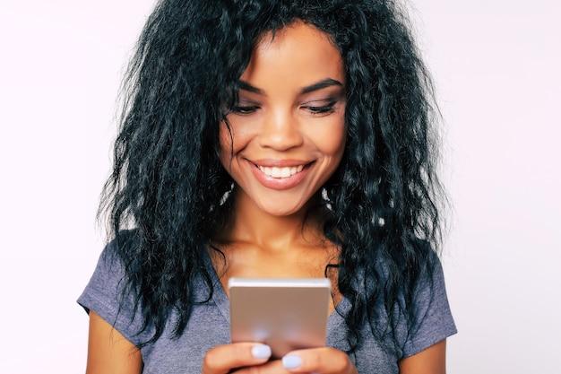 Макро портрет афро-женщины с широкой манящей улыбкой и длинными вьющимися волосами, которая выражает счастье, читая что-то на своем смартфоне