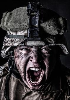 검은 배경에 땀에 젖은 더러운 얼굴 스튜디오 촬영으로 위장 헬멧을 쓰고 미친 듯이 소리치는 특공대원으로 공격하는 공격적인 비명을 지르는 육군 군인의 초상화를 닫습니다