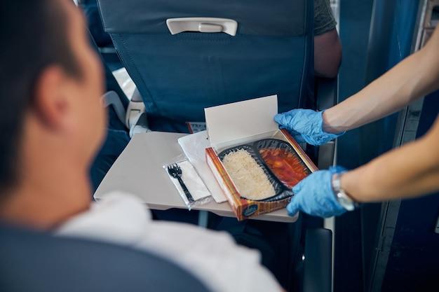 비행기 기내에서 코로나 바이러스 애정을 방지하기 위해 보호 장갑에 남성 승객을 위해 음식 상자를 제공하는 항공 스튜어디스의 초상화를 닫습니다