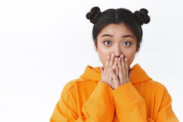 驚いて驚いた若い感情的なアジアの女の子のクローズアップの肖像画は、無言でカメラを見つめ、畏敬の念を抱いて口に手をつないで、大きな恐ろしいニュースを聞いて、驚きの反応を示し、白い背景