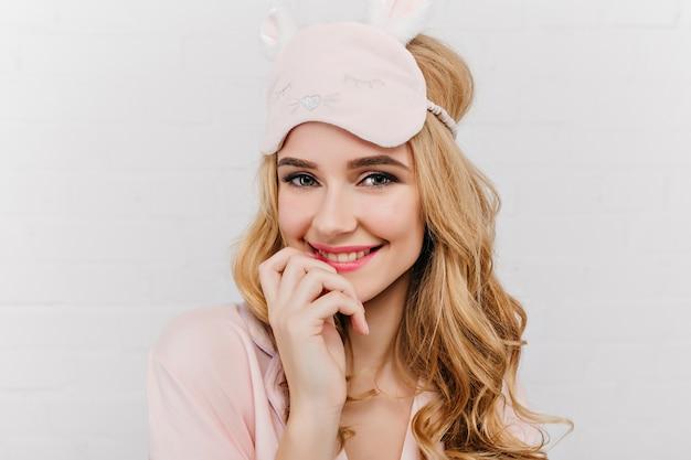 Макро портрет удивительной голубоглазой молодой женщины в модной eyemask. на фото в помещении чувственная кудрявая белая женщина-модель в розовой маске для сна.
