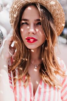 Крупным планом портрет удивительной европейской женщины с милой прической, позирующей с выражением заинтересованного лица. прелестная кавказская девушка в соломенной шляпе, глядя.