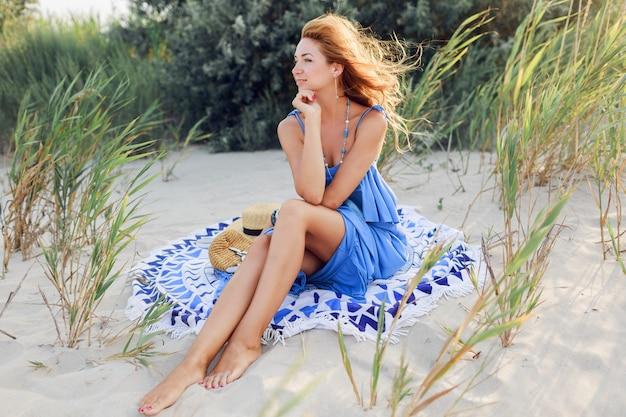 タオルの上の春の太陽が降り注ぐビーチでリラックスした青いドレスの素晴らしい笑顔赤毛の女性の肖像画を閉じます。麦わら帽子、スタイリッシュなブレスレット、ネックレス。