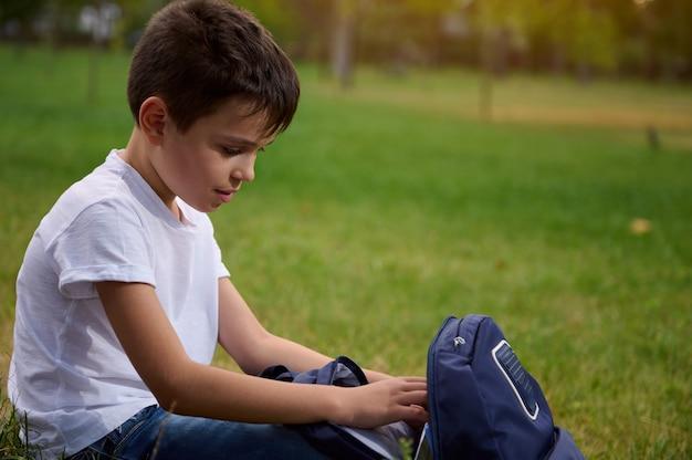 放課後の休憩中に公園に座って、ランドセルで仕事の本や物資を探しているオープンバックパックを持つ愛らしい男子生徒のクローズアップの肖像画。学校に戻るコンセプト