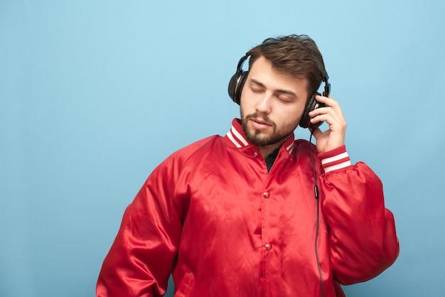 Крупным планом портрет взрослого мужчины слушает музыку в наушниках с закрытыми глазами на синем