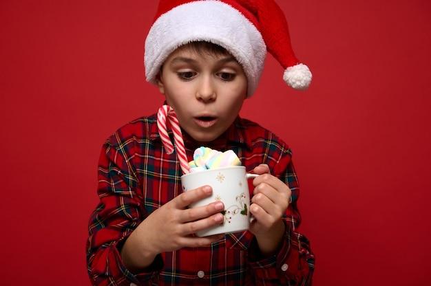 Крупным планом портрет изумленного мальчика, с удивлением смотрящего на кружку с горячим шоколадным напитком, украшенную зефиром, сладким леденцом из тростника леденца. рождественская концепция на красном фоне с пространством для рекламы