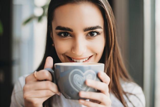 커피 숍에서 그녀의 입술 근처에 뜨거운 커피 한 잔을 들고 웃 고있는 카메라를보고 놀라운 백인 여자의 초상화를 닫습니다.