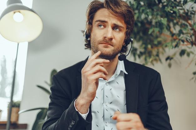 ストレスの多い迷惑なオンライン会話をしているヘッドセットで怒っているビジネスマンの肖像画を閉じる