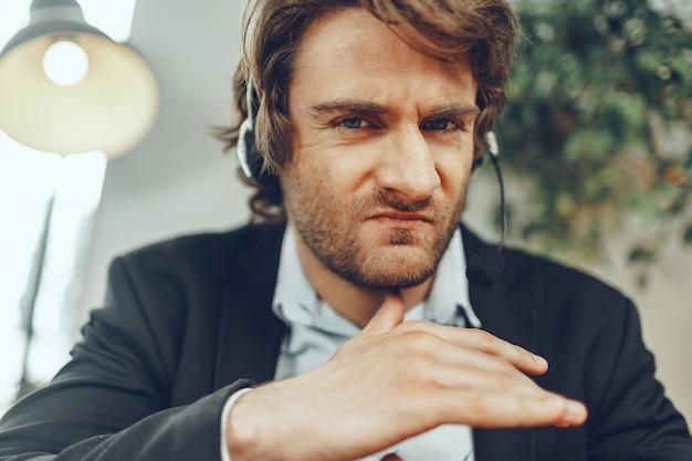 ストレスの多いオンライン会話を持つヘッドセットで怒っているビジネスマンの肖像画を閉じる