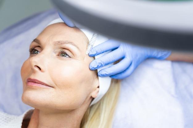 Крупным планом портрет привлекательной блондинки с мечтательным взглядом, получающей инъекции