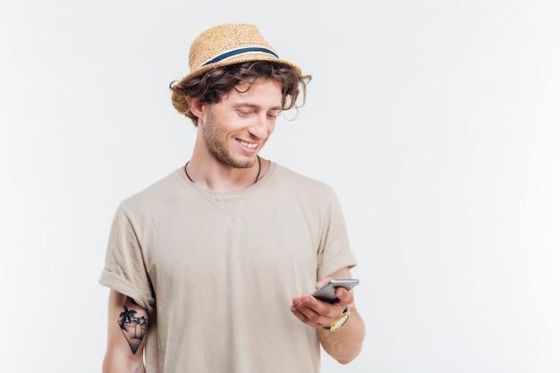 Крупным планом портрет привлекательного хипстерского человека, отправляющего текстовые сообщения с помощью мобильного телефона, изолированного на белом фоне