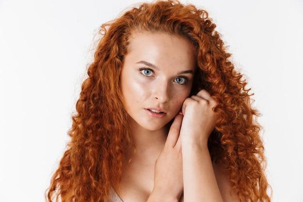 Крупным планом портрет привлекательной чувственной молодой женщины с длинными вьющимися рыжими волосами, стоя изолированными