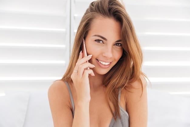 Крупным планом портрет привлекательной улыбающейся девушки в бикини, говорящей по телефону