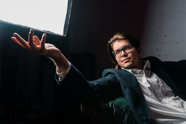 ソファでリラックスできる魅力的な若い男のクローズアップの肖像画