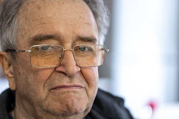 眼鏡をかけた年配の男性のポートレートを閉じます。