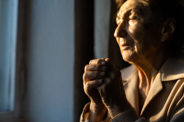 기도하는 늙은 여자의 초상화를 닫습니다