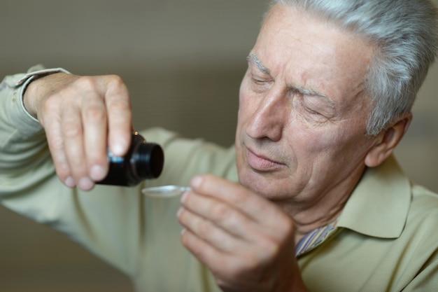 약을 복용하는 노인의 클로즈업 초상화