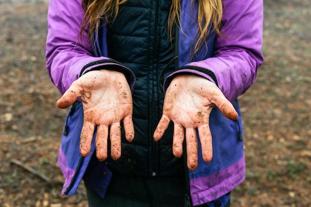 森の中をトレッキングしている間、汚れでいっぱいの彼女の手のひらを見せている認識できない女性の肖像画をクローズアップ
