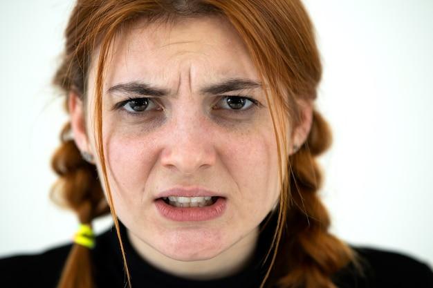 Закройте вверх по портрету злой рыжей девочки-подростка.