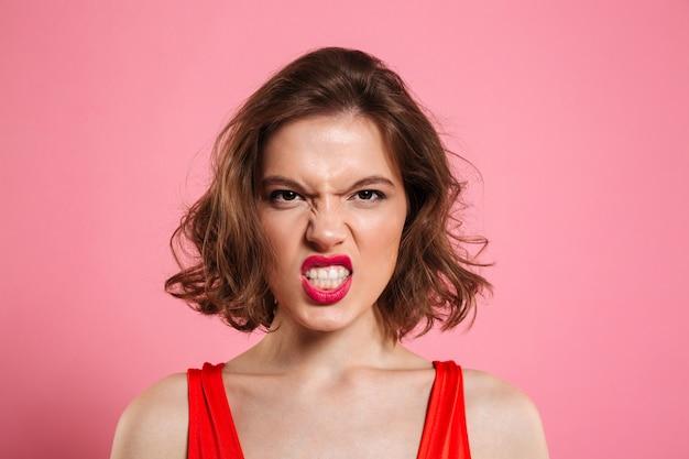 赤い唇と怒っている若い女性のクローズアップの肖像画