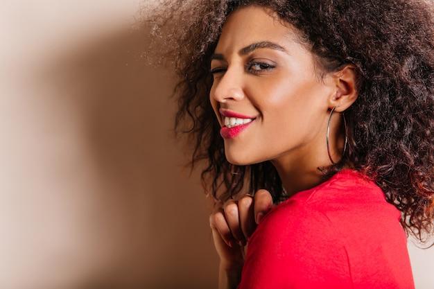 魅力的な若い女性のクローズアップの肖像画はイヤリングを着ています