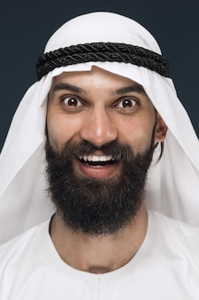 ダークブルーのスタジオの背景にアラビアのサウジアラビアの実業家の肖像画を閉じます。立って笑顔の若い男性モデルは、幸せそうに見えます。ビジネス、金融、顔の表情、人間の感情の概念。