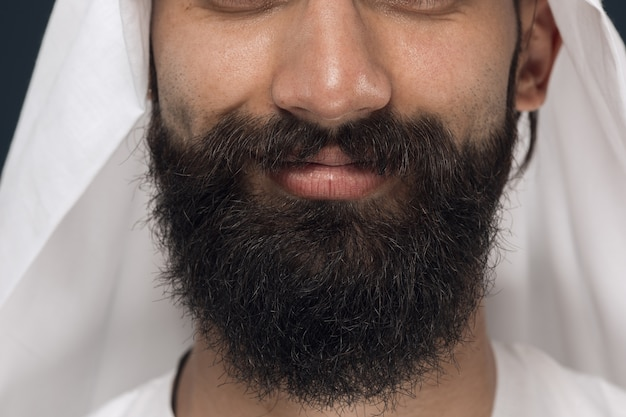 アラビアのサウジアラビアの実業家の肖像画を閉じます。若い男性モデルのひげ、笑顔で顔。ビジネス、金融、顔の表情、人間の感情の概念。